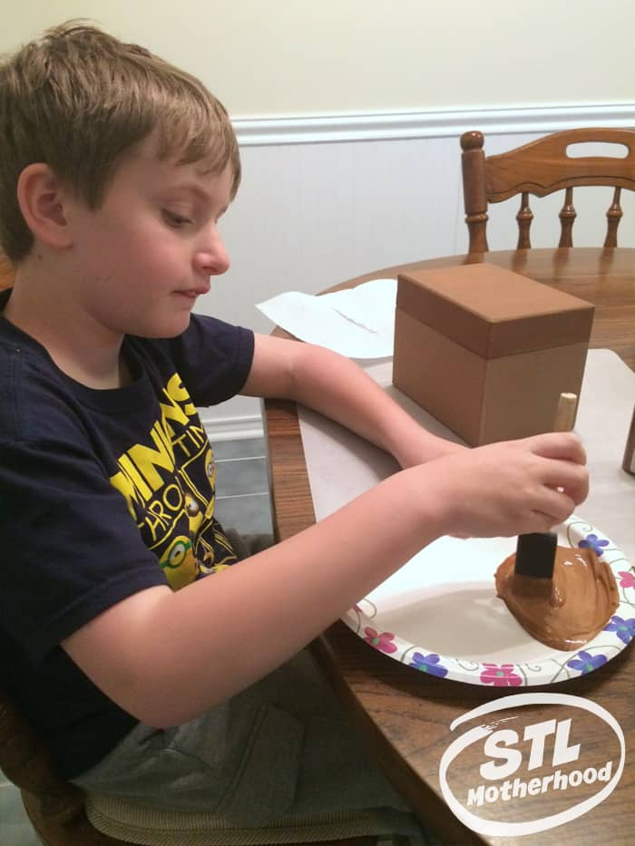 kid painting a box