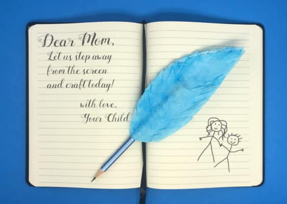 blue quill pencil made with a paper feather on an open journal
