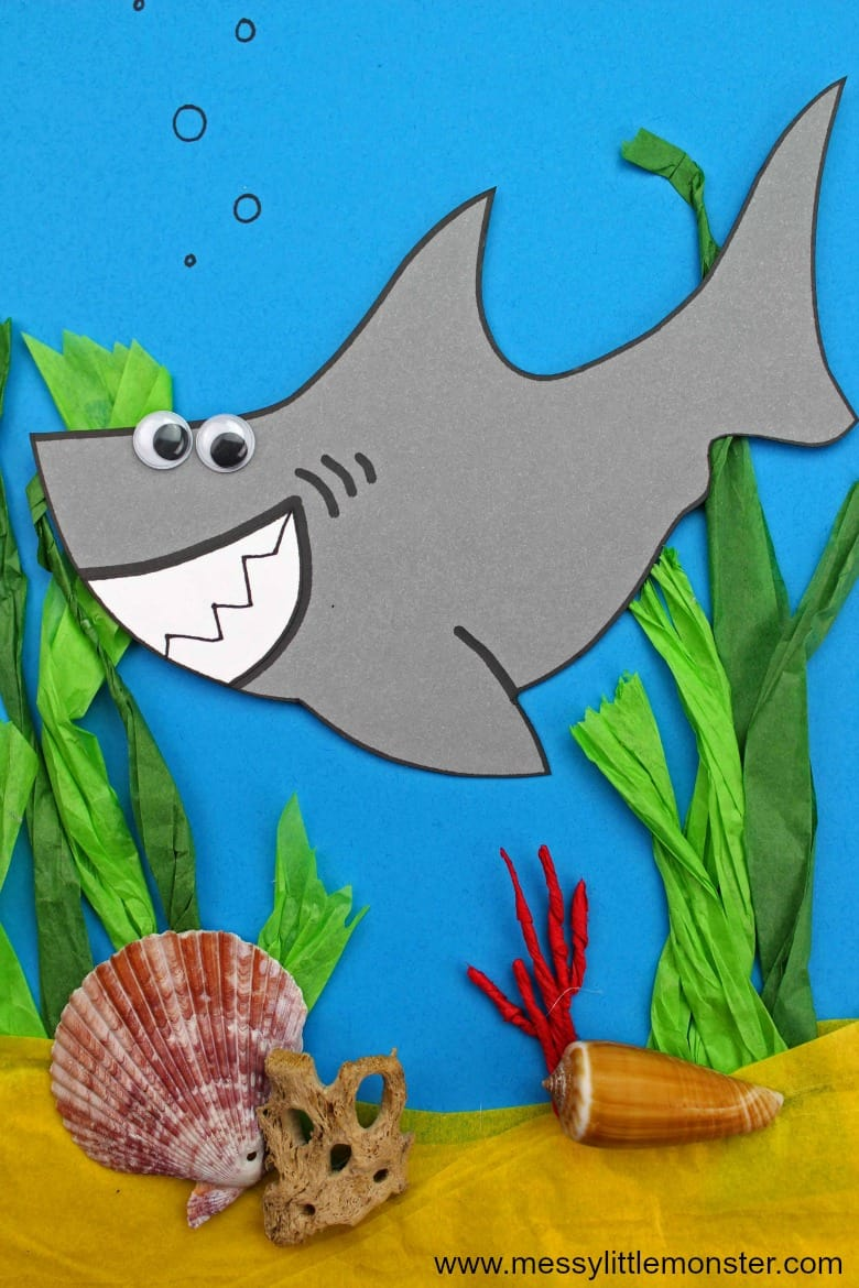 paper shark craft with googly eyes and tissue paper ocean background