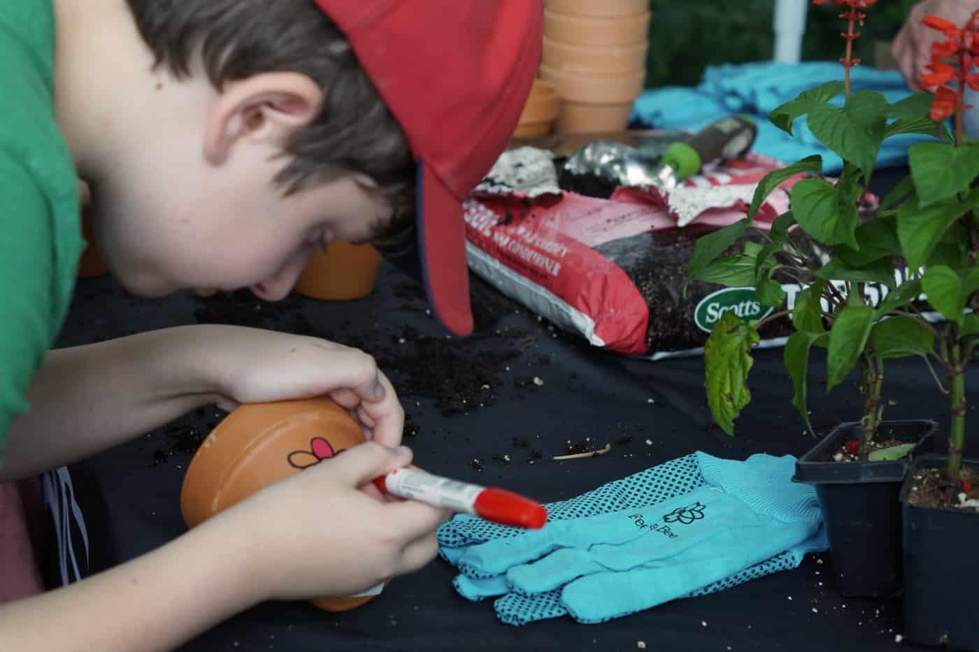 kid decorating a clay pot