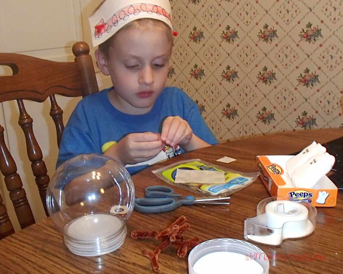 kid crafting for halloween while wearing silly hat