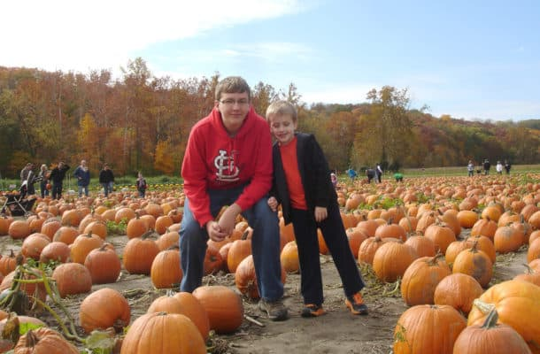 two brothers in a pumpkin field in St. Louis. One is wearing a Cardinals shirt