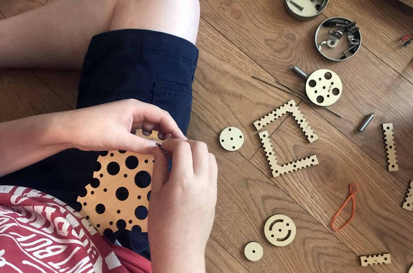 close up of boy working with Tinkering Labs kit, holding wooden parts