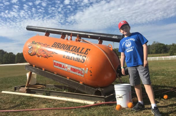 Kid in blue shirt by a giant air compressor powered pumpkin cannon.
