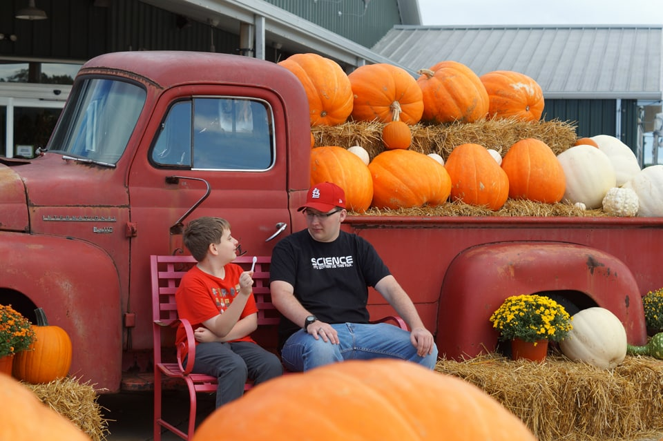 Two brothers in front of a classic red pickup full of pumpkins at Eckert's pick your own pumpkin patch in the St. Louis Area.