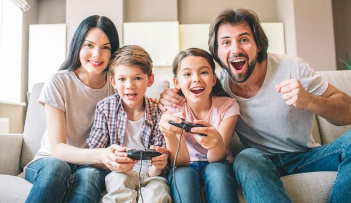 Amazing family sits on sofa. Children are playing on xbox. The game is intense. Guy rejoys. Girl is smiling as well. Mother helps to play her son