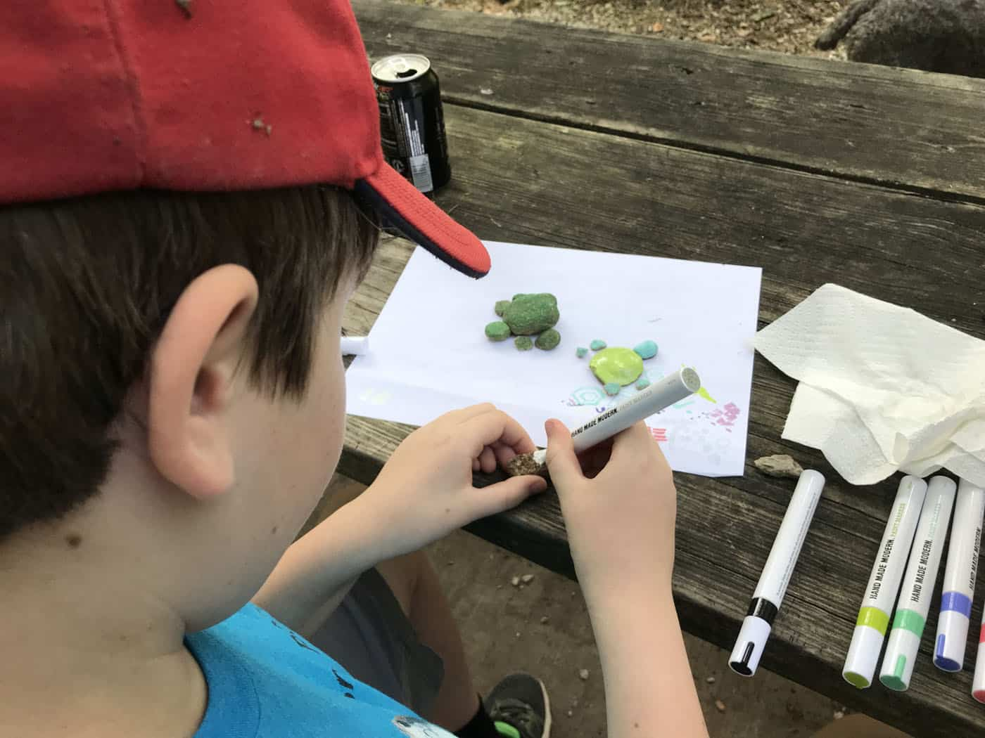 kid paints rocks with acrylic paint pen on a camping trip