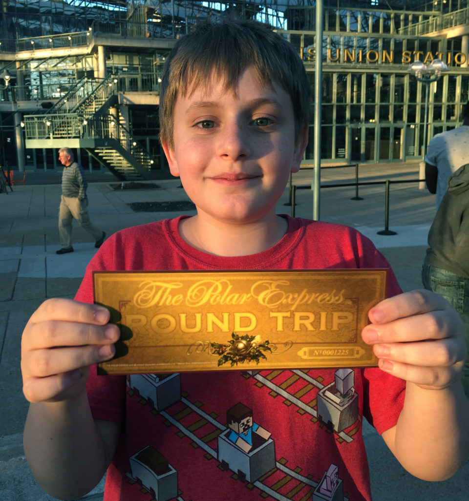 Boy in red shirt with golden Polar Express Ticket in St. Louis Union Station