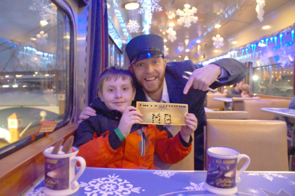 Boy in red coat with a Golden Polar Express Ticket and Mr. Conductor