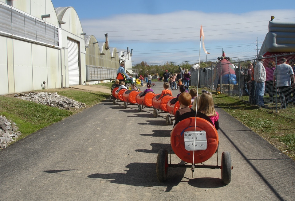 Kids riding a tractor pulled barrel train at Stuckmeyer Farm, a top St. Louis Pumpkin Patch