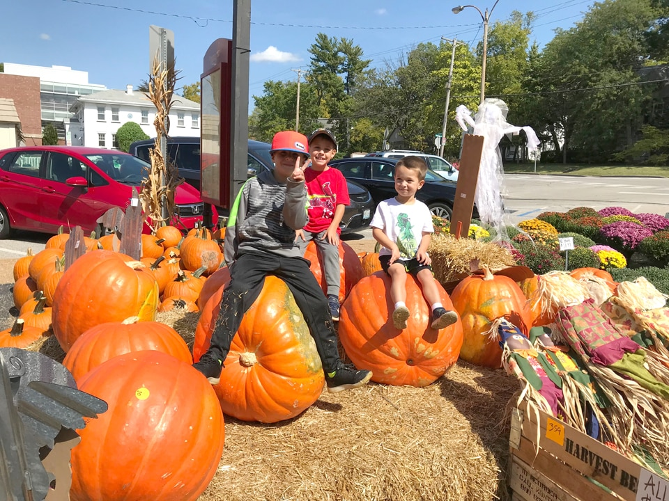 Summit Produce in Kirkwood, kids sitting on pumpkins