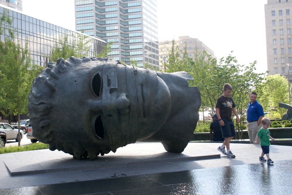Family visiting City Garden with giant steel statue of a head