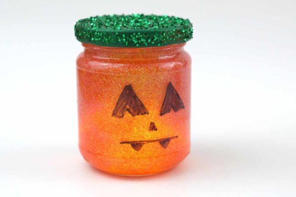 jar with glass painted to look like a pumpkin, green glitter on the lid