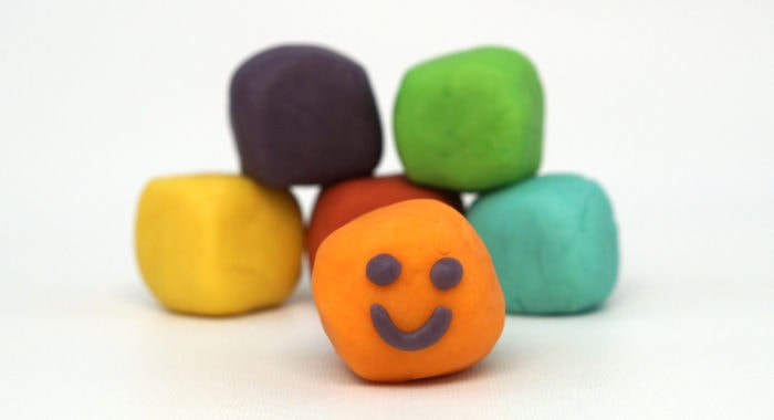 Rainbow of homemade playdough balls. The orange ball has a smiley face.