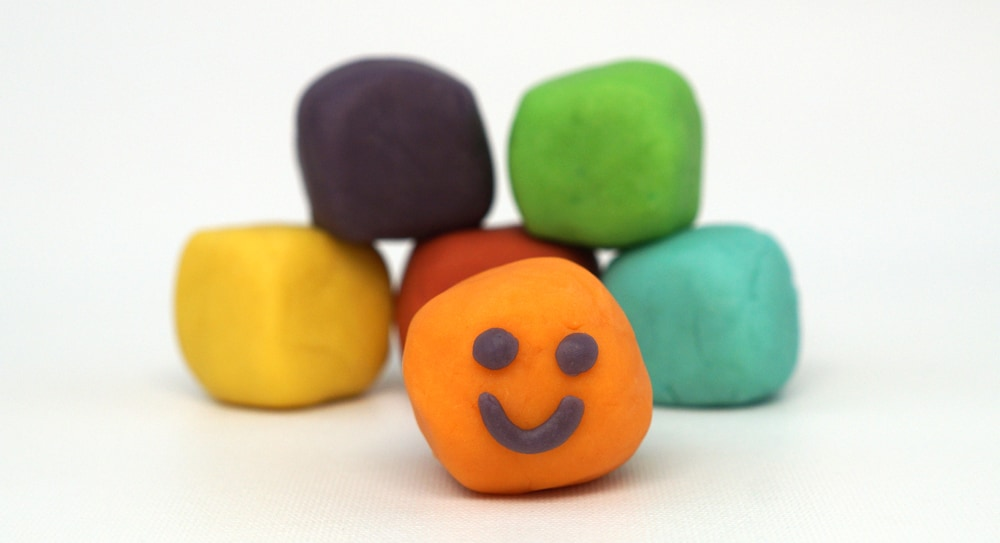 blocks of home made play dough in rainbow colors, the orange one has a smiley face