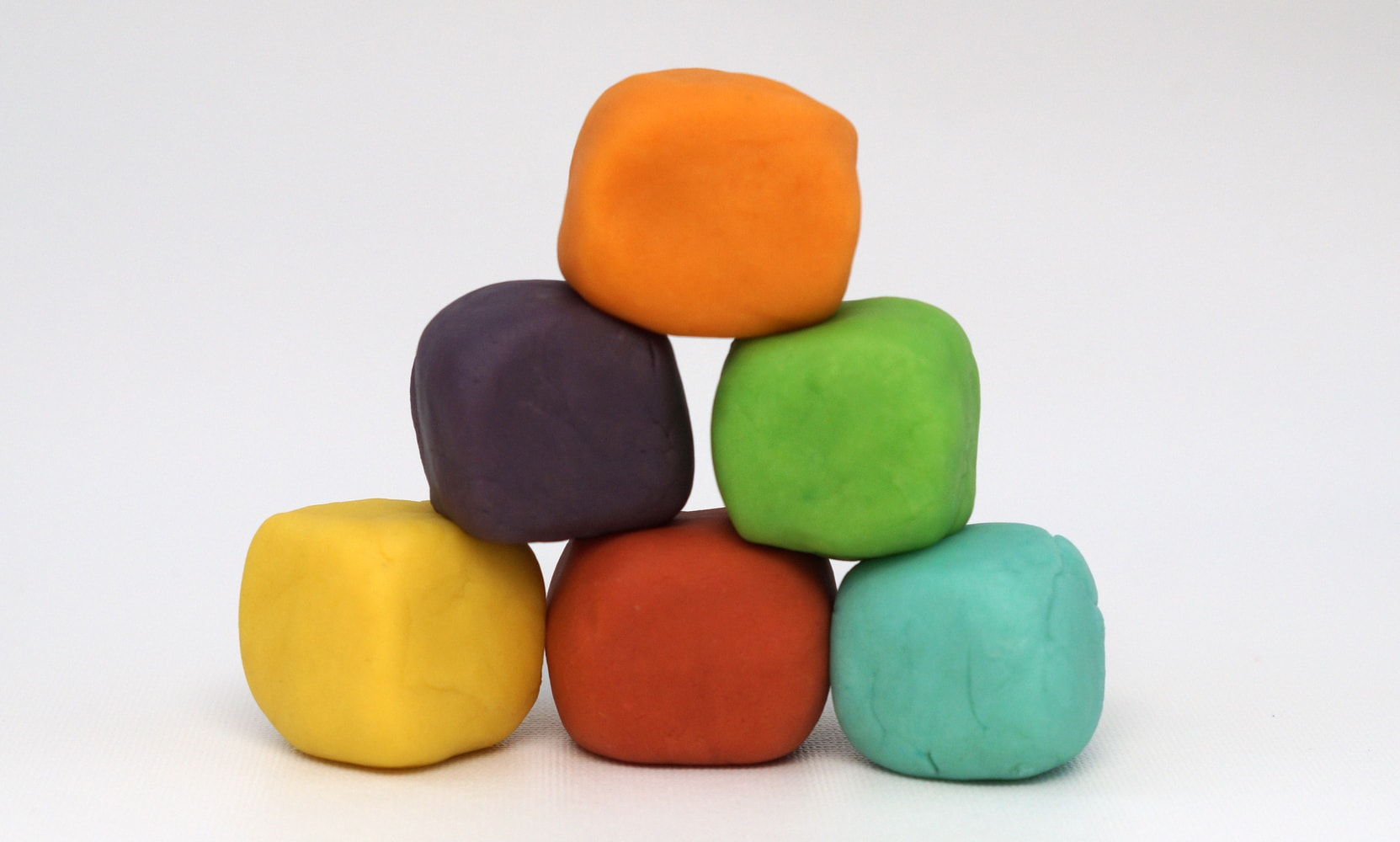 stack of homemade playdough cubes in a rainbow of colors
