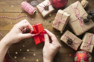 hands wrapping small gifts in red paper, brown paper wrapped gifts around it.