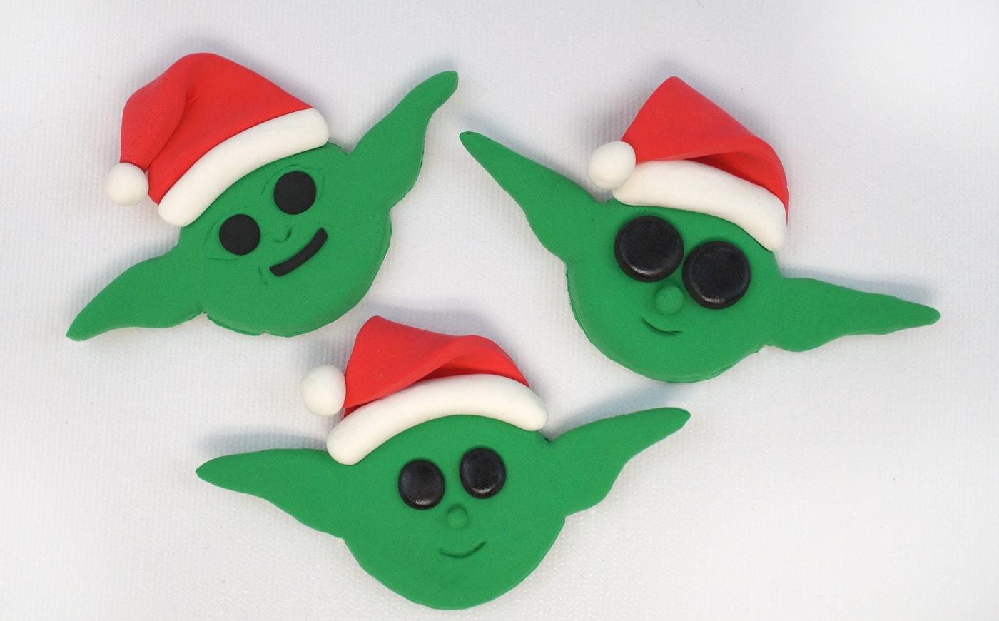 Three baby Yoda Christmas ornaments wearing Santa hats