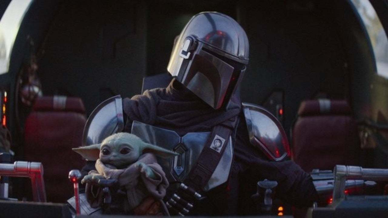 the Mandalorian and baby Yoda, with baby reaching for the ships controls