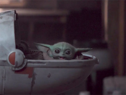 Baby Yoda looking happy in his floating bassinet