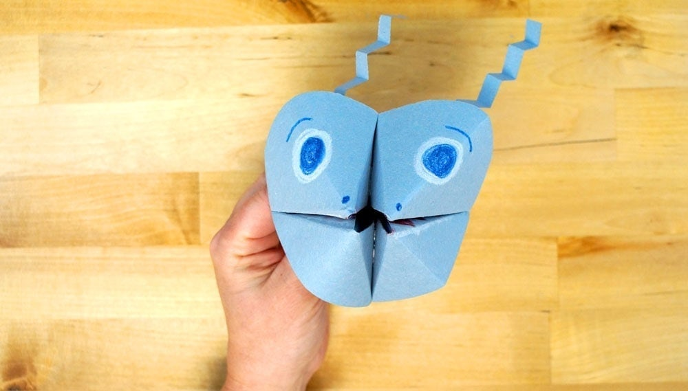 paper cootie catcher toy with a face