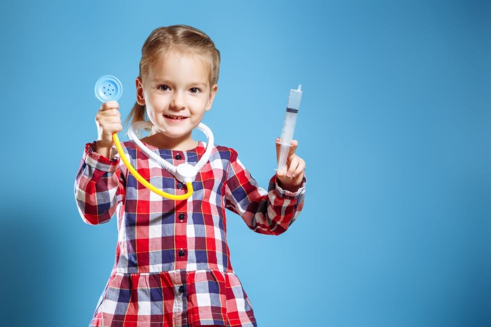 kid in plaid dress pretending to be a doctor