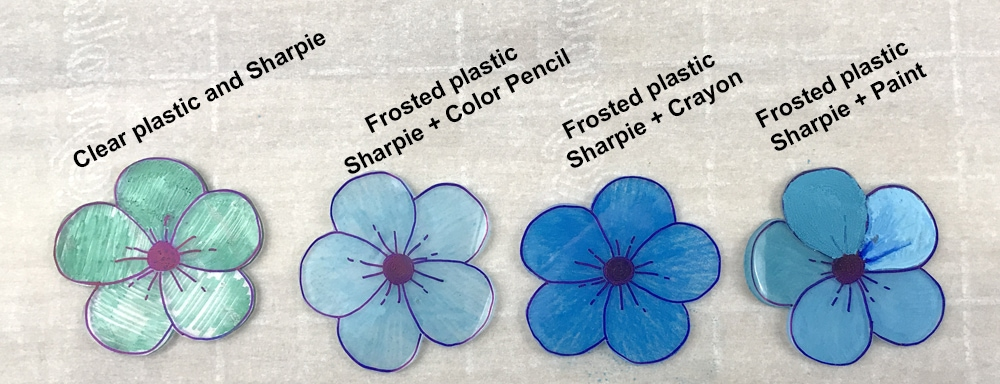 blue shrinky dink flowers colored in different mediums: sharpie, colored pencil, crayon, and paint