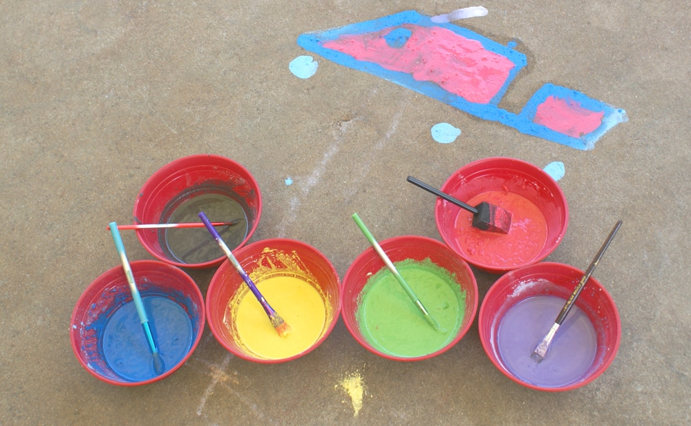 6 bowls of sidewalk chalk paint in blue, green, black, yellow, red and purple next to child's painting of a car