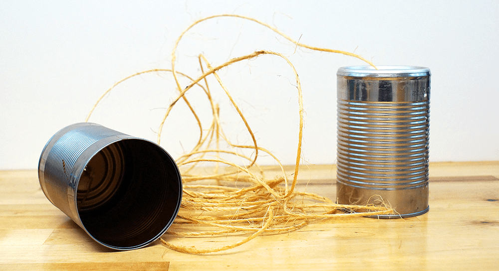 two clean soup cans with string running through them making a tin can telephone