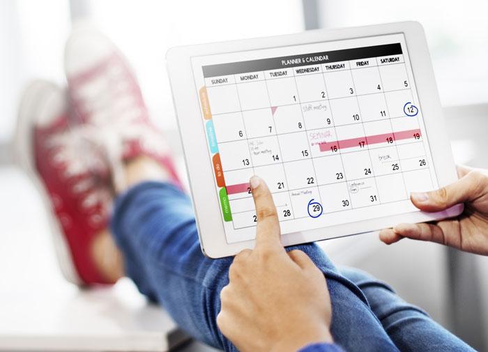 calendar on an ipad, feet up on a desk
