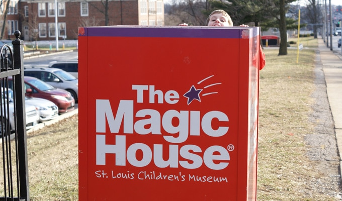 Kid peeking out behind the red Magic House sign