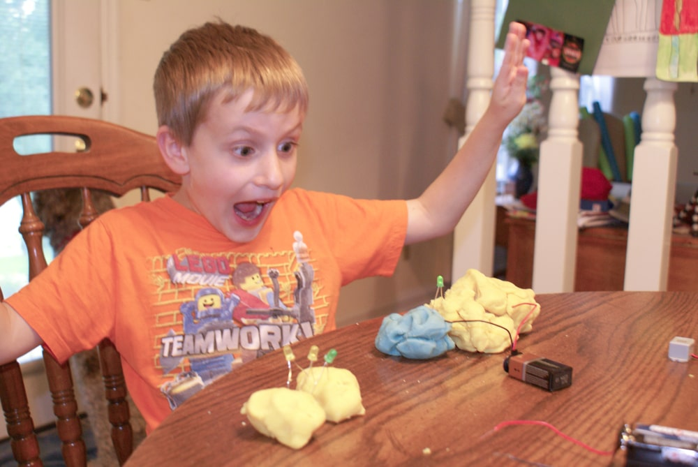 boy excited about electric playdough experiment with an LED light
