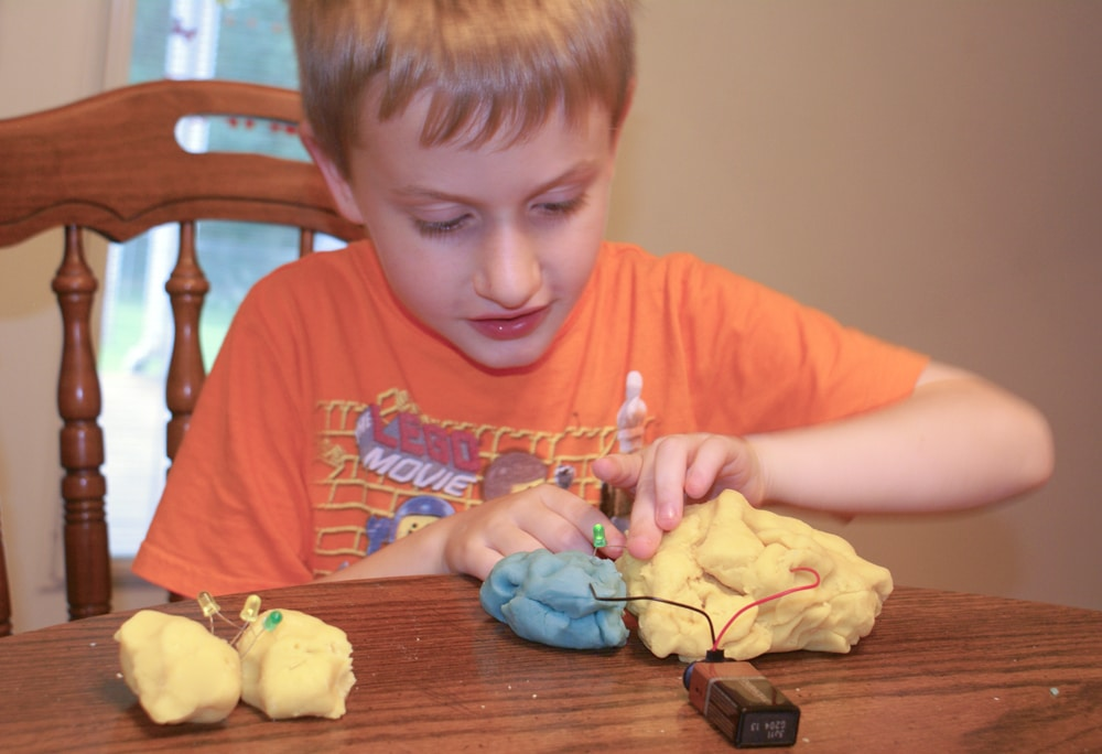 kid playing with electric play dough and making a circuit with LED lights