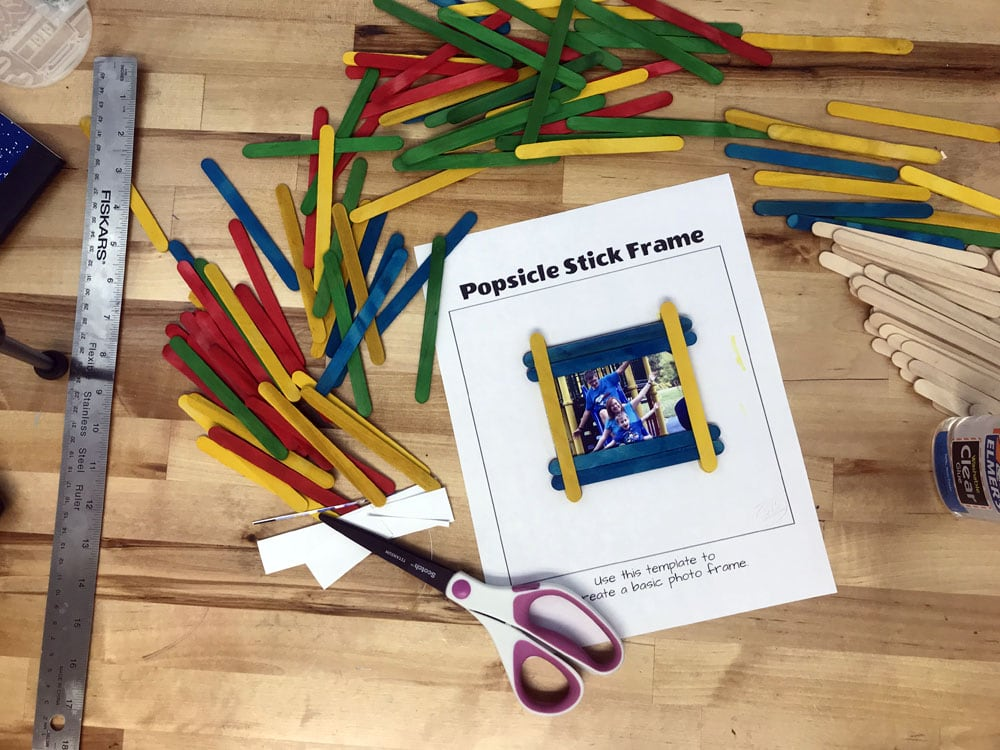finished craft stick photo frame surrounded by colorful Popsicle sticks
