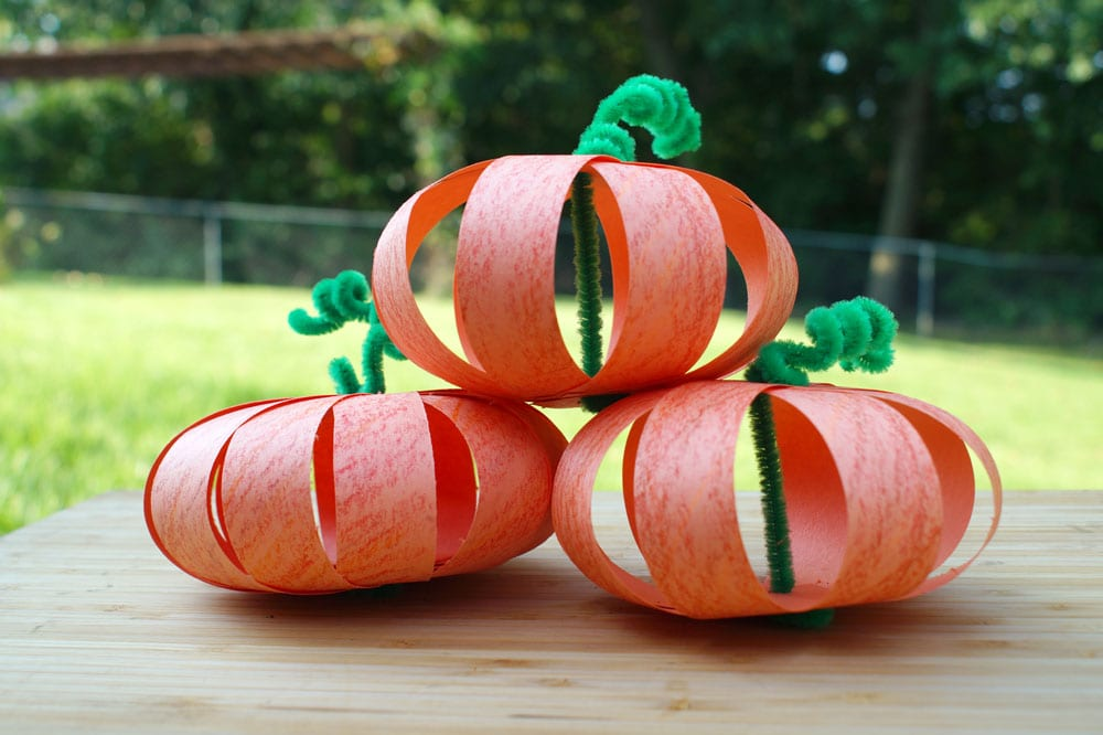 paper strip pumpkins made with orange paper and fuzzy sticks
