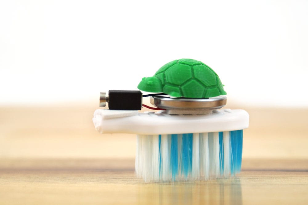 green plastic turtle on a brush bot made from a toothbrush