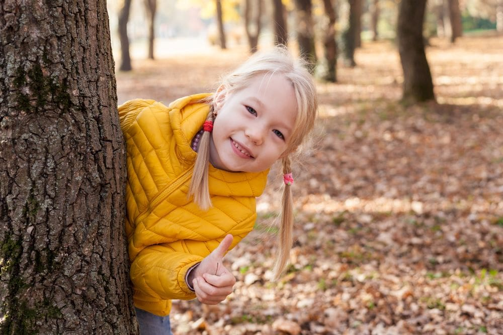 girl in yellow outside by a tree in the autumn