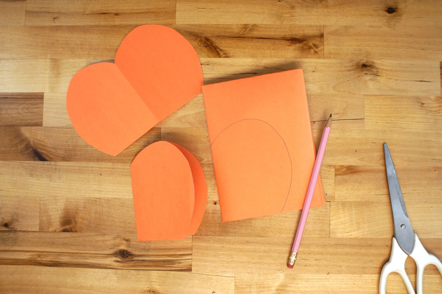How to make a 3D pumpkin with sheets of orange paper, pencil and scissors