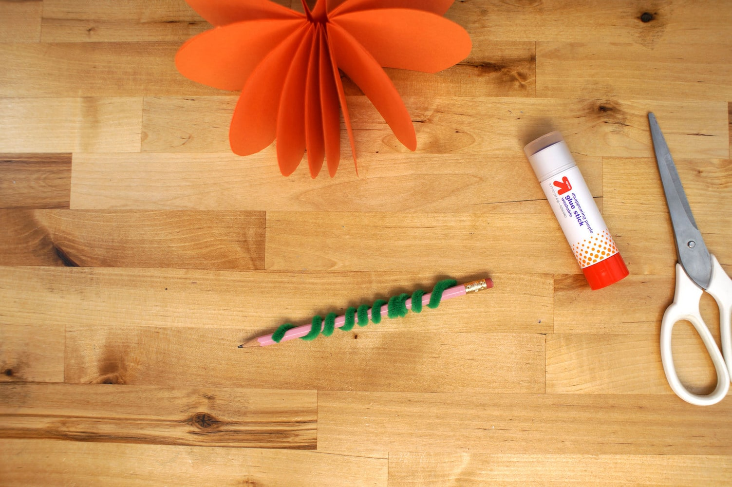 curl a green fuzzy stick around a pencil to form the stem of the pumpkin