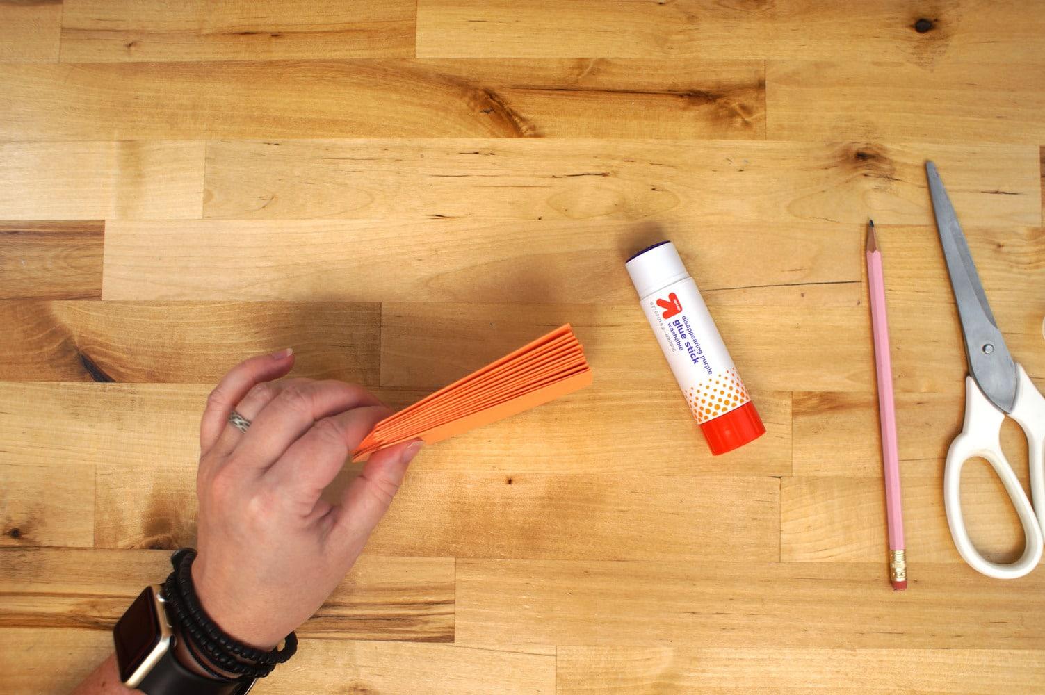 hand holding a stack of orange paper pumpkin slices together for gluing