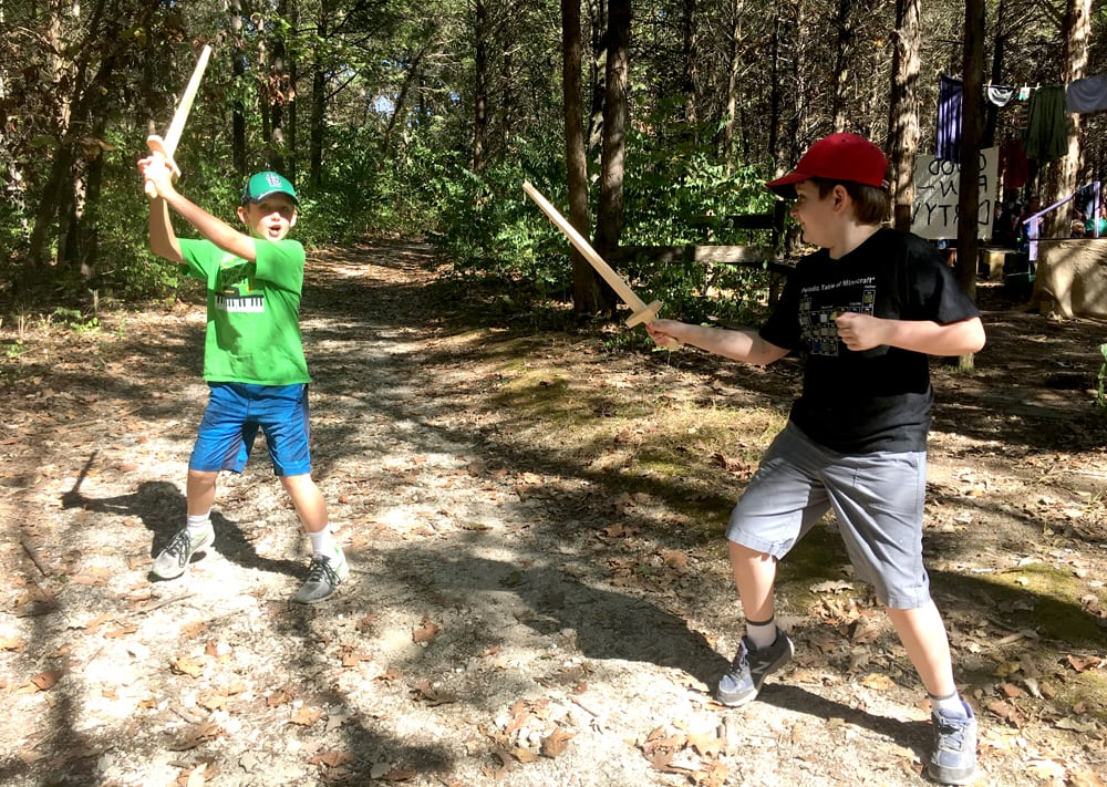 two boys in the woods play with wooden swords at the St. Louis Renaissance festival