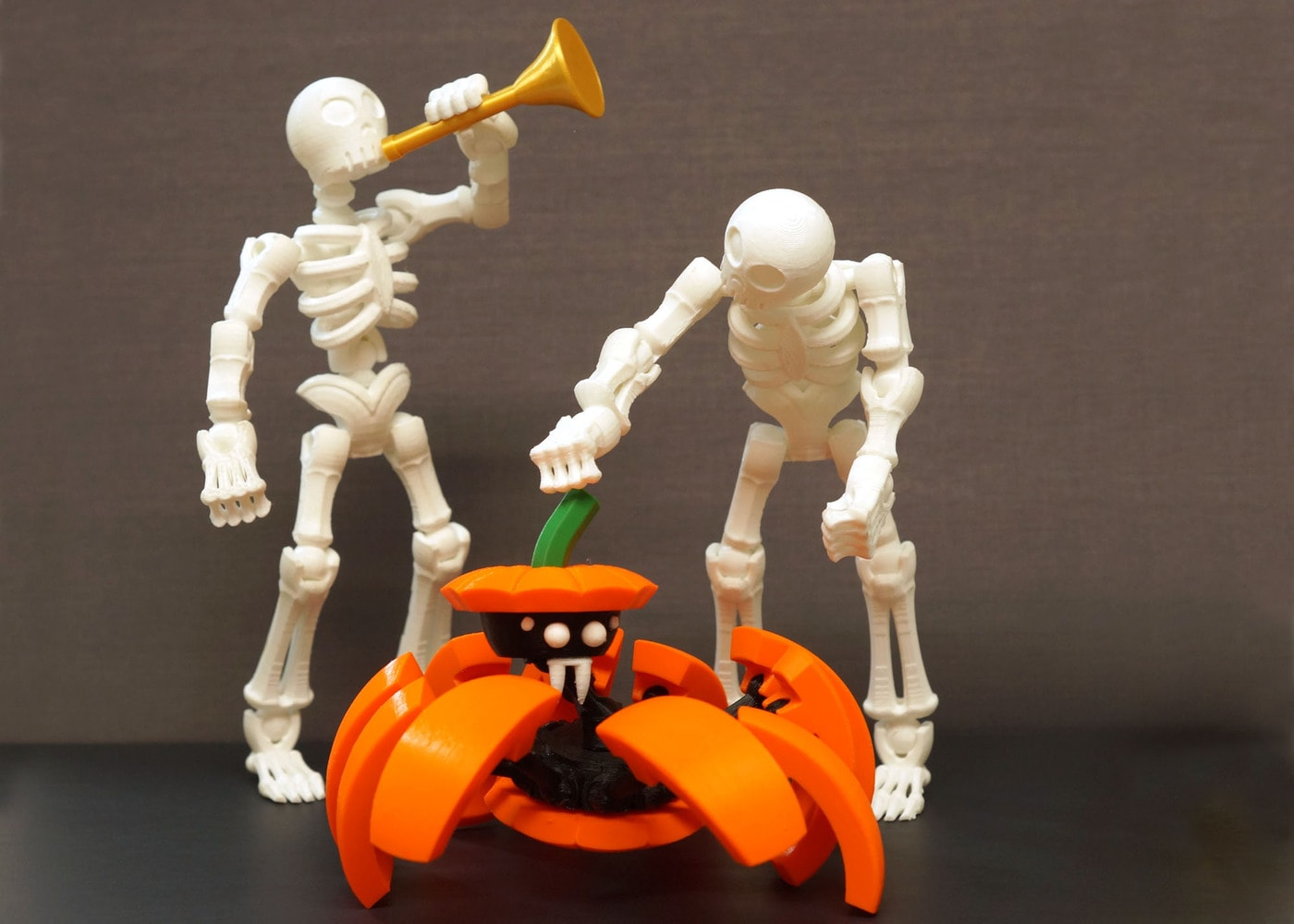 3d printed Halloween toys: two skeleton action figures and a pumpkin spider transformer