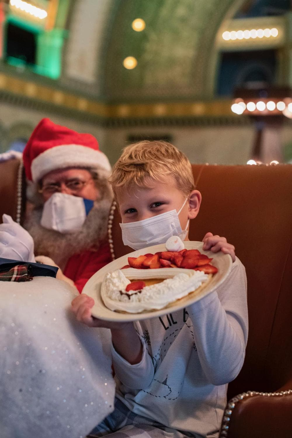 Kid in mask with pancake and Santa