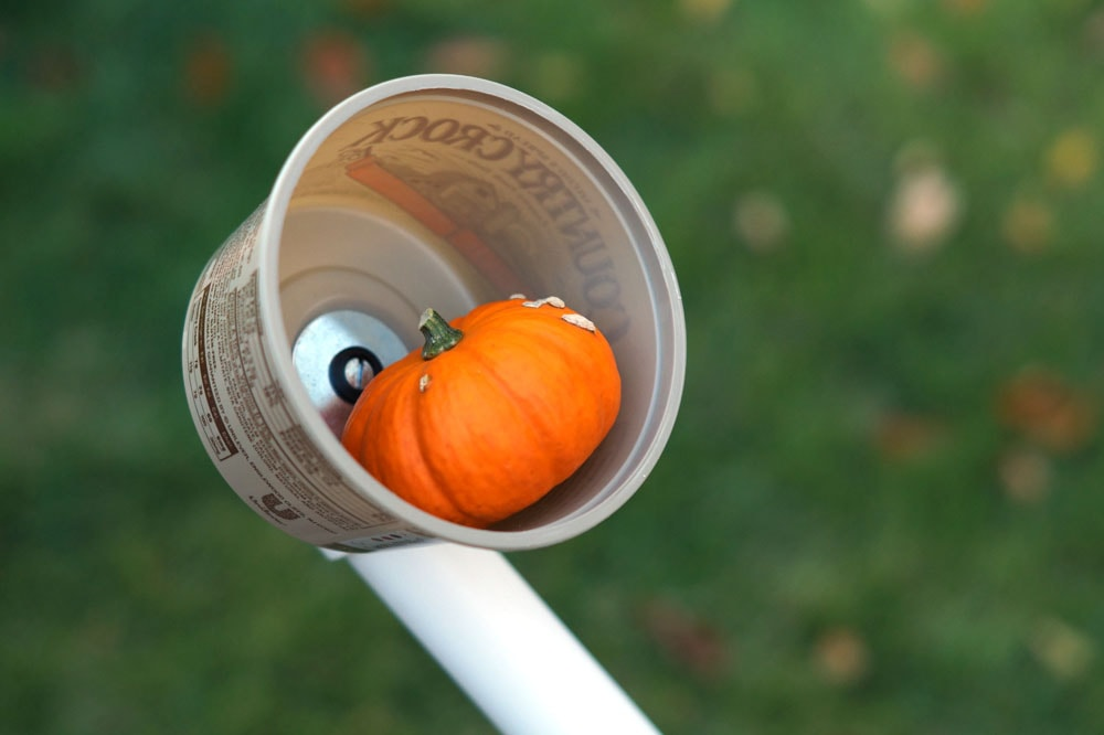 small pumpkin in a pvc catapult basket made from a butter tub