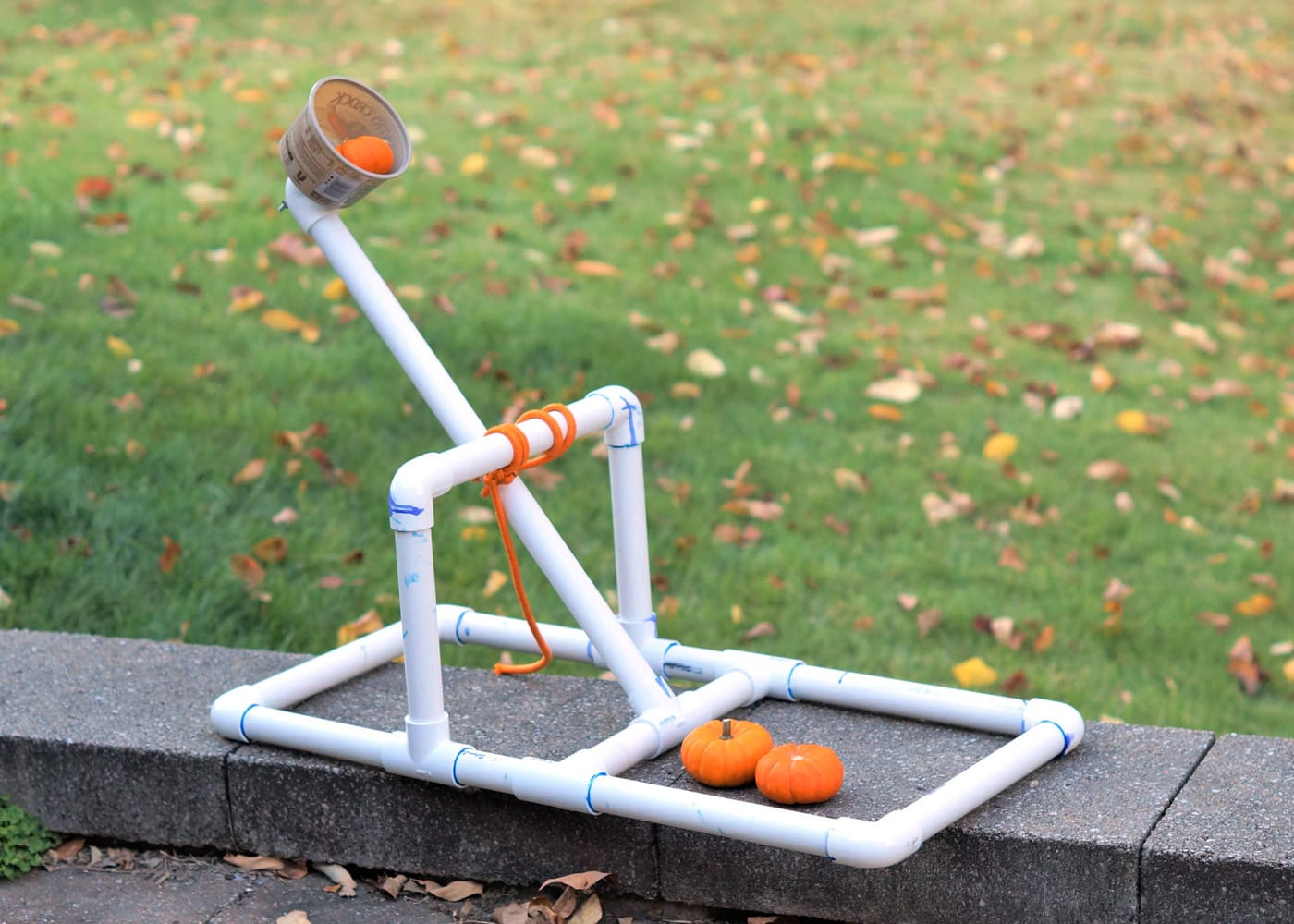 "catapult made from white pvc pipe with a small butter tub ""basket"" and a small pumpkins"