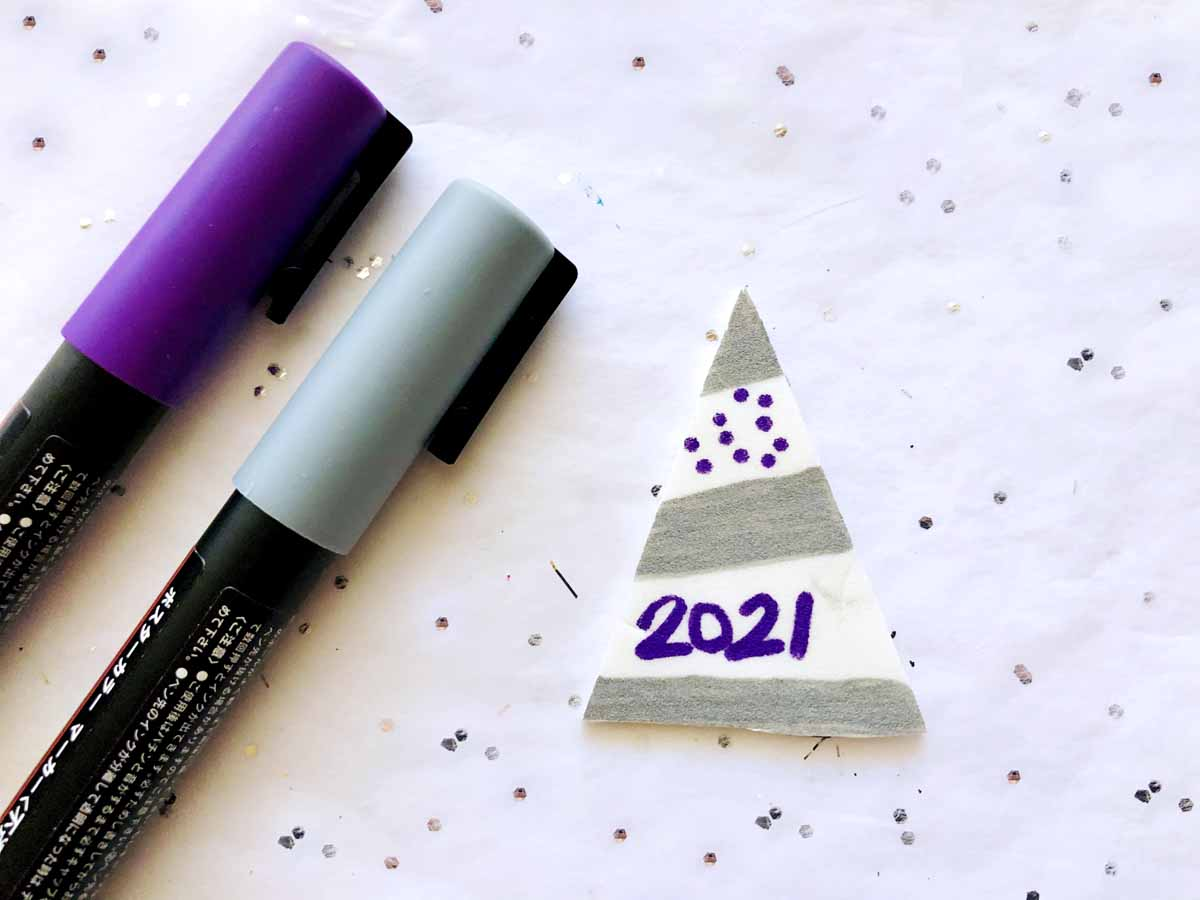 decorate a new years noise maker with a tiny party hat