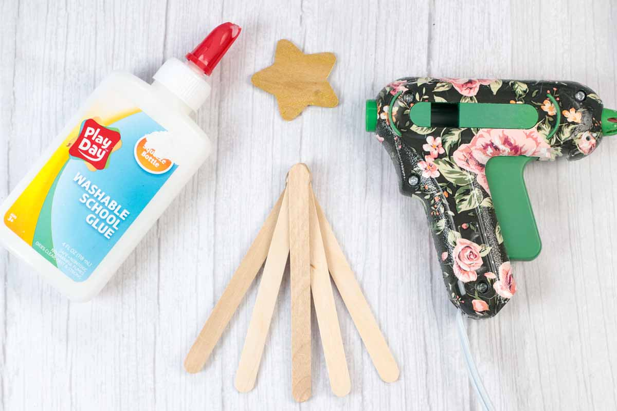 making a popsicle stick and pom pom Christmas tree