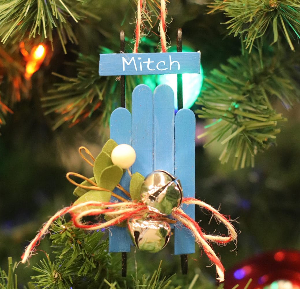 blue popsicle stick sled with jingle bells on a Christmas tree