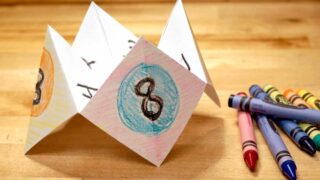 paper fortune teller next to crayons